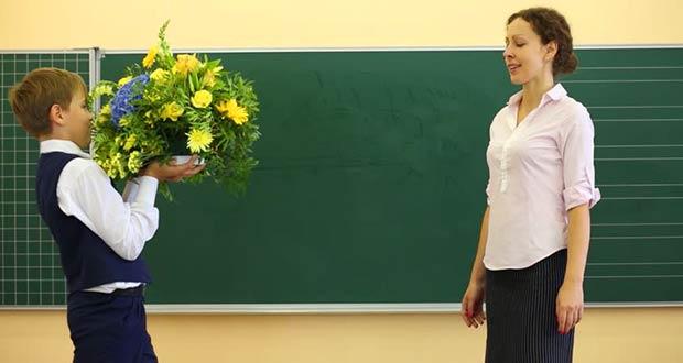 Ученик дарит красивый букет цветов учителю