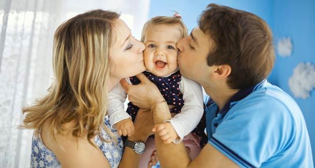 Молодые родители целуют свою дочку