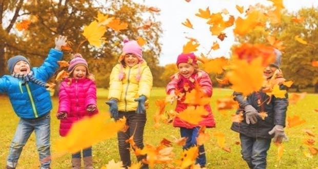 Дети подбрасывают листья