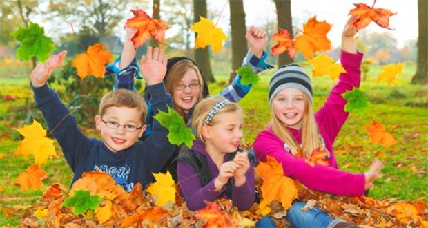 Дети подбрасывают желтые листья