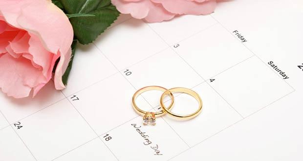 Свадебные кольца и розы лежат на календаре