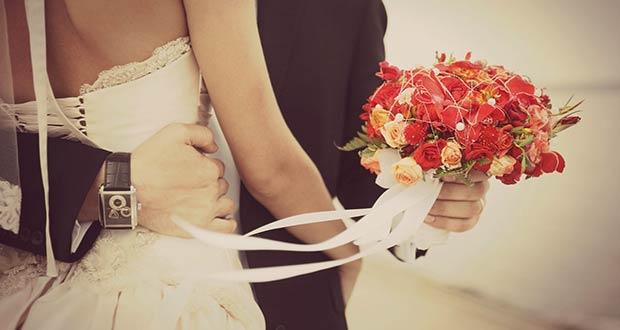 Жених с цветами обнимает невесту