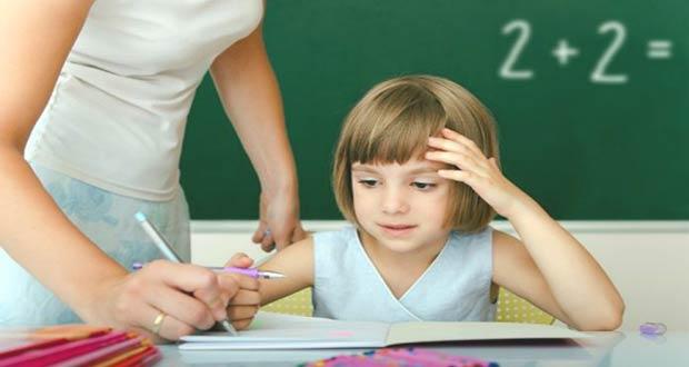 Учительница проверяет задание у первоклассницы